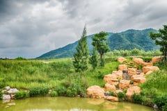 La hermosa vista de un pequeño lago afiló por los árboles verdes Foto de archivo