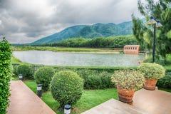 La hermosa vista de un pequeño lago afiló por los árboles verdes en el otoño Imagenes de archivo