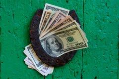 La herradura vieja y dólar americano Fotografía de archivo