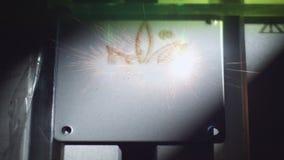 La herramienta del laser hace que la flor representa el grabado en la placa almacen de metraje de vídeo