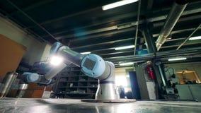 La herramienta robótica de trabajo hace girar en una tabla en una planta almacen de metraje de vídeo