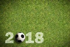La hierba con 2018 roció el texto y un balón de fútbol Imagenes de archivo