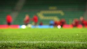 La hierba del campo de fútbol con lluvia cae con proceso unfocused del entrenamiento del equipo en el fondo