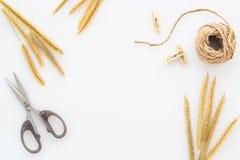 La hierba seca, una bobina de la cuerda y scissor aislado en una tabla blanca, materiales caseros de DIY para la creatividad y un fotos de archivo libres de regalías