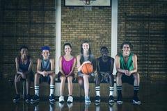 La High School scherza la seduta su un banco nel campo da pallacanestro fotografie stock