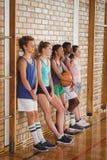 La High School secundaria embroma inclinarse contra la pared en cancha de básquet Fotografía de archivo libre de regalías