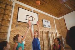 La High School secundaria emocionada embroma anotar una meta mientras que juega a baloncesto Imagenes de archivo
