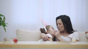 La hija acomete en los brazos del ` s de la madre en casa y le da un abrazo grande El padre feliz está besando a su hija