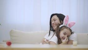 La hija acomete en los brazos del ` s de la madre en casa y le da un abrazo grande Están mirando en la cámara y dan gomoso