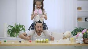 La hija adorable y alegre se está sentando en los hombros de su padre Ella está saltando primero, y en seguida comienza a bailar