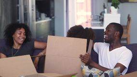 La hija africana del niño salta de juego de la caja con los padres metrajes