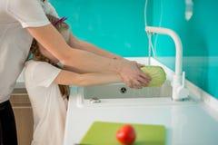 La hija ayuda a la madre en la cocina, serie de la foto de la forma de vida en interior casero brillante fotos de archivo