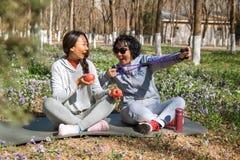 La hija ayuda a su madre con ejercicios en el parque imagen de archivo libre de regalías