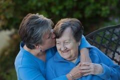La hija besa la frente de las madres Fotografía de archivo
