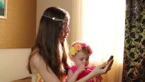 La hija compone los labios con el lápiz labial a la mamá Mime a los juegos con su hija en el cuarto de niños cerca de la ventana almacen de metraje de vídeo