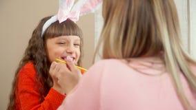 La hija con los oídos y la mamá del conejito con una mano a aferrarse al azul del huevo del pollo, y la mamá dibuja en él una lín metrajes