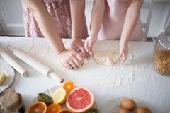 La hija con la mamá amasa la pasta para las galletas Foto de archivo