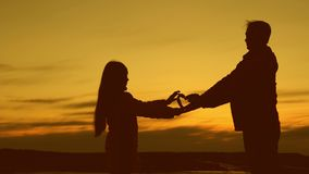 La hija da a papá un símbolo del corazón en la puesta del sol Concepto de familia feliz la hija de amor estira hacia fuera el cor almacen de metraje de vídeo