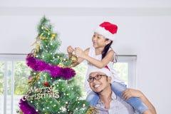 La hija de ayuda del padre adorna el árbol de navidad Foto de archivo