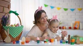 La hija de enseñanza de la madre adorna los huevos, familia en la venda linda que se sienta en la tabla almacen de metraje de vídeo