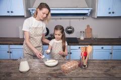 La hija de la mam? y del ni?o en la cocina est? preparando la pasta, cociendo las galletas La mam? ense?a a su hija a amasar la p imagen de archivo