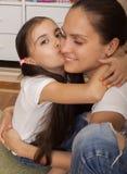 La hija el adolescente besa a la madre en una mejilla Imágenes de archivo libres de regalías