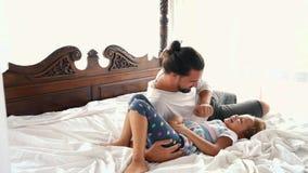 La hija feliz del pequeño niño del idilio de la familia salta el la caída de Arms And They del padre en una cama almacen de metraje de vídeo