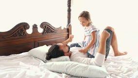 La hija feliz del pequeño niño del idilio de la familia salta el la caída de Arms And They del padre en una cama metrajes