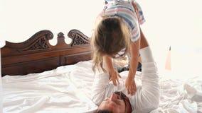 La hija feliz del pequeño niño del idilio de la familia salta el la caída de Arms And They del padre en una cama almacen de video