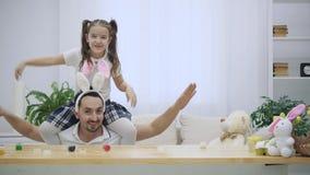 La hija feliz y alegre se está sentando en los hombros y el baile de su padre El padre se está sentando debajo de la tabla de mad