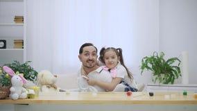 La hija feliz y alegre se está sentando en los hombros y el baile de su padre El padre se está levantando de madera