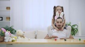 La hija feliz y alegre se está sentando en los hombros y el baile de su padre El padre se está sentando en la tabla de madera