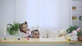 La hija feliz y alegre se está sentando en los hombros y el baile de su padre El padre está sentando el unter la tabla de madera