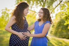 La hija hispánica siente al bebé golpear adentro la panza de la madre con el pie embarazada Imagen de archivo
