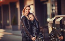 La hija joven abraza a la madre en la ciudad del otoño al aire libre Fotos de archivo