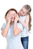 La hija joven cierra a la mamá de los ojos de las manos Fotografía de archivo