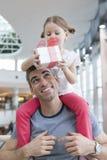 La hija joven se sienta en hombros de los padres y le da un presente Imagen de archivo