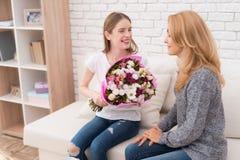 La hija le da las flores de la madre Imagen de archivo