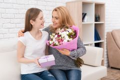 La hija le da las flores y los regalos de la madre Fotografía de archivo libre de regalías