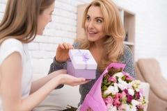 La hija le da las flores y los regalos de la madre Foto de archivo libre de regalías