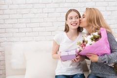 La hija le da las flores y los regalos de la madre Fotos de archivo libres de regalías