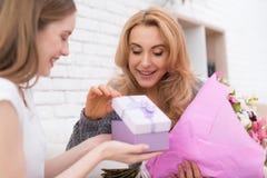 La hija le da las flores y los regalos de la madre Imagen de archivo libre de regalías