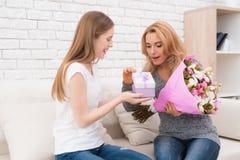 La hija le da las flores y los regalos de la madre Fotografía de archivo