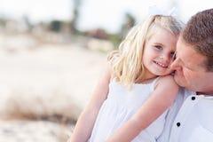 La hija linda abraza para arriba con ella en la playa imagen de archivo