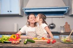 La hija linda besa a la mamá en su mejilla mientras que cocina en una cocina azul hermosa fotos de archivo