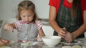 La hija linda está ayudando a sus padres al cocinero El proceso de cocinar Poca ayuda almacen de video