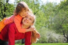 La hija miente en la madre encendido detrás en resorte Imagen de archivo libre de regalías