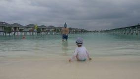 La hija mira al papá flotante en una máscara cerca de la orilla metrajes