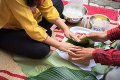 La hija que aprende hacer que Chungkin se apelmaza por las manos con su primer del padre, torta de Chungkin es el vietnamita trad Fotos de archivo libres de regalías