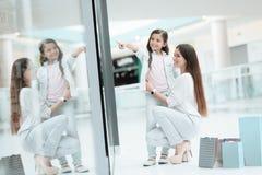 La hija se está sentando en el revestimiento de la madre en centro comercial La mamá y la muchacha están sonriendo fotos de archivo libres de regalías